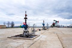 Green and red pumpjack, oil horse, oil derrick pumping oil well with dramatic cloudy sky background stock images