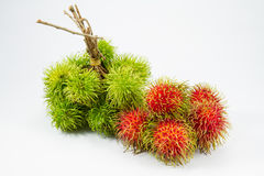 Green and red rambuton on white backgruond. Royalty Free Stock Photography