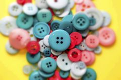 Green and red sewing buttons on yellow Stock Photography