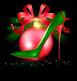 Green red shoe and festive ball. Black background and the large red Christmas ball with abstract festive green womans shoe Royalty Free Stock Images