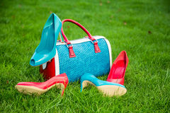 Green and red shoes and bag lay on the grass. Two pairs of green and red shoes and bag lay on the grass Royalty Free Stock Photo