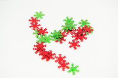 Green Red Snowflake Embellishments. Bright colourful shiny snowflake embellishments. Small red and green snowflakes on white background isolated Stock Photos