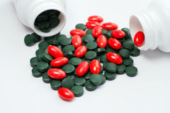 Green and red tablets. Spilling out of container Stock Images