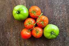Green and red tomatoes on a wooden background Stock Image
