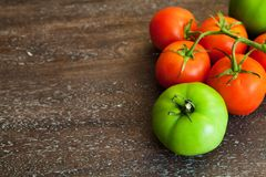 Green and red tomatoes on a wooden background Royalty Free Stock Photo