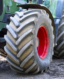 Green and red tractor with big wheels and selective focus. Tractor on a construction area Stock Images