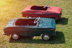 Green and red vintage toy cars on a green grass field. Side view. Sunset light Stock Photos