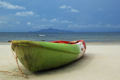 The green-red-white boat on the sand beach with sea and a mountain and blue sky on background. Royalty Free Stock Photos