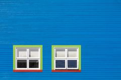 Green and red windows on blue wall. Green, red and white windows on a blue wooden wall. Minimalism style of the houses of Iles de la Magdalen, Canada, in bright royalty free stock photography