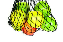 Green, red and yellow apples in in mesh bag  Stock Image