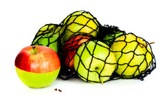Green, red and yellow apples in in mesh bag  Royalty Free Stock Photos