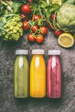 Green,red and yellow colorful organic vegetables, fruits and berries smoothies with ingredients in bottles on gray granite table stock images