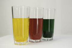 Green, red, yellow, juice, glasses. On white background Royalty Free Stock Images