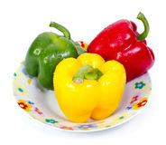 Green red and yellow paprika(capsicum) on plate Royalty Free Stock Photos