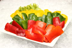 Green, red and yellow peppers Stock Images