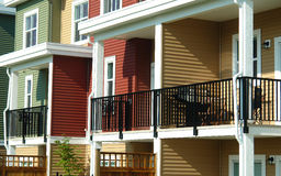 Green Red Yellow Row Houses Balconies. Back yard balconies of bright colored townhomes Stock Photos