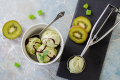 Green refreshing pistachio ice cream in white bowl. On a blue background Royalty Free Stock Image
