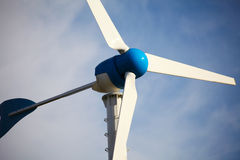 Green renewable energy concept - wind generator turbines on blue Stock Images