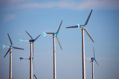 Green renewable energy concept - wind generator turbines on blue Royalty Free Stock Photo