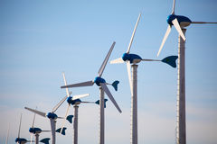 Green renewable energy concept - wind generator turbines on blue Stock Image