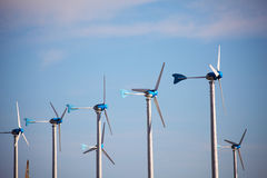 Green renewable energy concept - wind generator turbines on blue Stock Photos