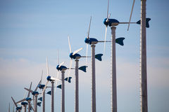 Green renewable energy concept - wind generator turbines on blue Royalty Free Stock Images