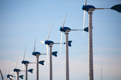 Green renewable energy concept - wind generator turbines on blue Royalty Free Stock Photography