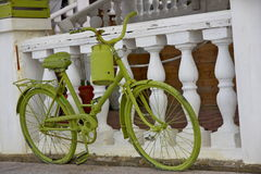 Green retro bike with watering can. Standing near fence royalty free stock images