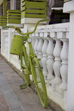 Green retro bike with watering can. Standing near fence stock photography