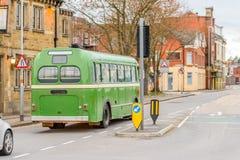 Green retro bus on British road in England.  Stock Photo