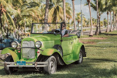 Green retro classic car with a young taxi driver Royalty Free Stock Photos