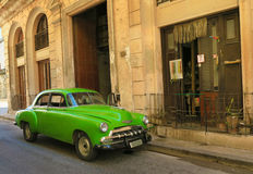 Green retro vintage car in Havana, Cuba. Cuba, Havana - 07 April, 2016: a green beautiful glossy retro car in the streets of Havana, waiting for its owner to Stock Photos