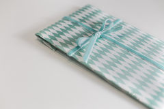 Green rhombus wrap paper gift on a white background Stock Photography