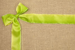 Green ribbon. Green ribbon on brown texturen textile with copyspace for your text Royalty Free Stock Photo