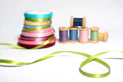 Green ribbon close-up with spools of threads Royalty Free Stock Photos