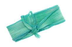 Green ribbon cloth material tied on white background Royalty Free Stock Image