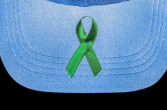 The green ribbon, kidney cancer awareness symbol. On a jean cap Stock Images