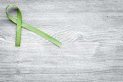 Green ribbon for Lyme disease, kidney cancer, organ donation awareness on grey wooden background top view copyspace. Green ribbon for Lyme disease, kidney cancer stock photography