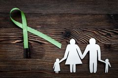 Green ribbon for Lyme disease, kidney cancer, organ donation awareness near paper silhouette of family on dark wooden. Background top view royalty free stock images