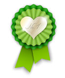 Green ribbon rosette with golden heart Stock Photos
