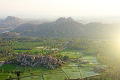 Green rice fields or terraces in the village of Hampi. Palm trees, sun,rice fields, large stones in Hampi. Tropical exotic. Landscape. Beautiful green valley royalty free stock photography