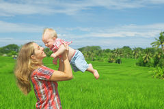 On green rice terraces background mother tossing joyful baby boy. Happy mother tossing up joyful baby boy on Balinese green rice terraces background. Outdoors Stock Photography