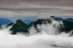 Green ridges in clouds, Carnic Alps Friuli Venezia Giulia Italy. Green ridges of Carnic Alps in clouds with radar station near Monte Terzo and Cimone di Royalty Free Stock Photo