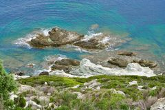 Green riff in front of a turquois sea. Green riff in front of a green-turquois sea with rocks in the water stock images