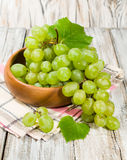 Green ripe grapes in a wooden bowl Royalty Free Stock Image