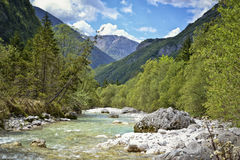 Green river valley in the Alps. Look at the clean,beautiful river unlimited slides, flows down the valley through large rocks in alpine valley .Peaceful and Royalty Free Stock Photography