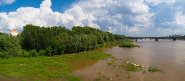 Green riverbank in Warsaw, Poland. Panoramic view from Świętokrzyski bridge. Hot air ballon in background Royalty Free Stock Photography
