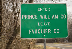 Green road sign in Virginia. Showing the border between Fauquier and Prince William Counties stock image
