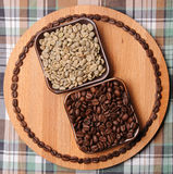 Green and roasted coffee beans in two square bowls on wooden board with circuit of the coffee beans. On plaid background. Green and roasted coffee beans in two stock images