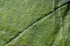 Green Rock - Diagonal Crack. Closeup of a green rock with a diagonal crack stock photo